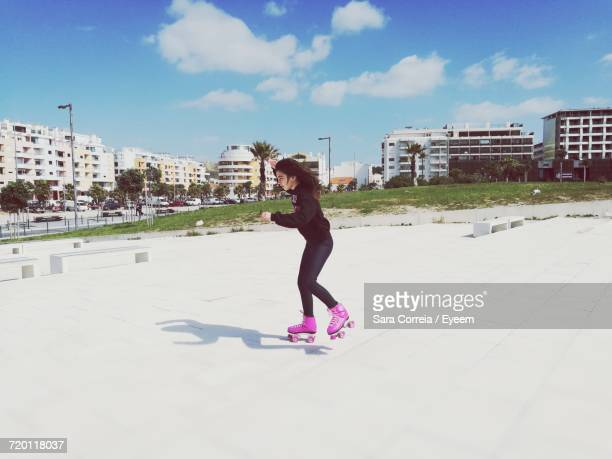 Side View Of Girl Roller Skating On Field Against Cloudy Sky