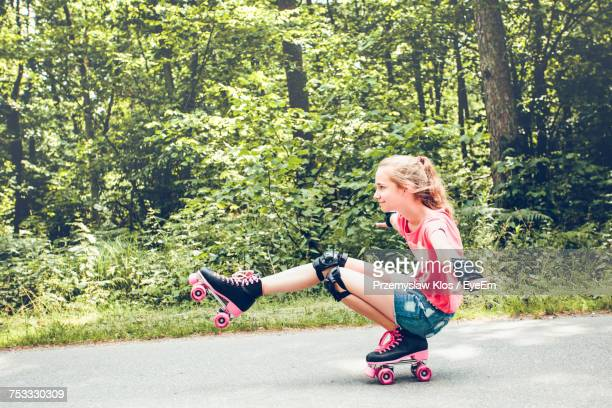 Side View Of Girl Roller Skating On Road Against Forest