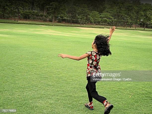 Side View Of Girl Running On Grassy Field At Park