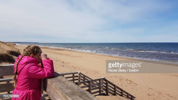 side view of girl shielding eyes while standing by railing at beach - sibley stock photos and pictures
