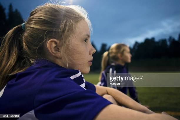 Side view of girl sitting at soccer field against sky