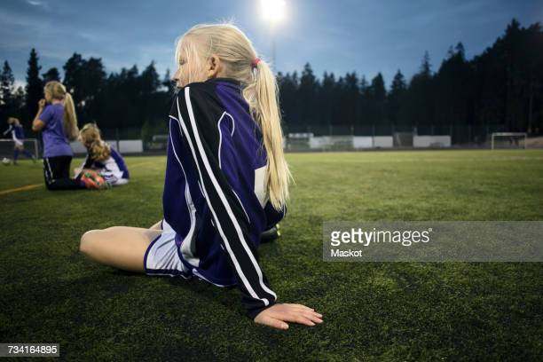 Side view of girl sitting on field against sky