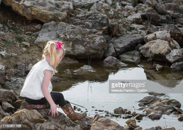 Side View Of Girl Sitting On Rock At Lakeshore