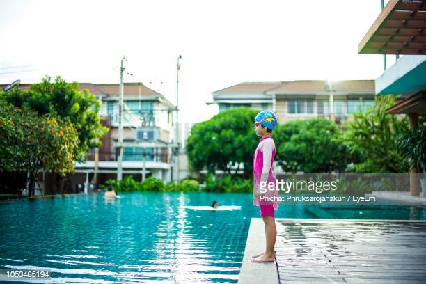 Side View Of Girl Standing By Swimming Pool