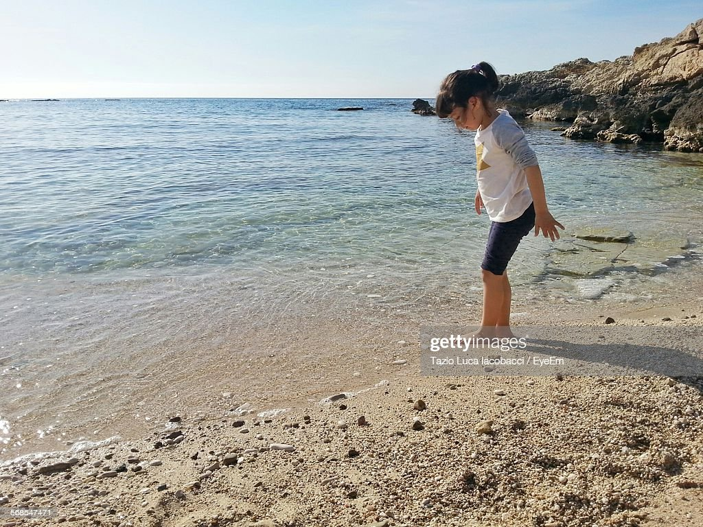 Side View Of Girl Standing On Beach : Stock Photo