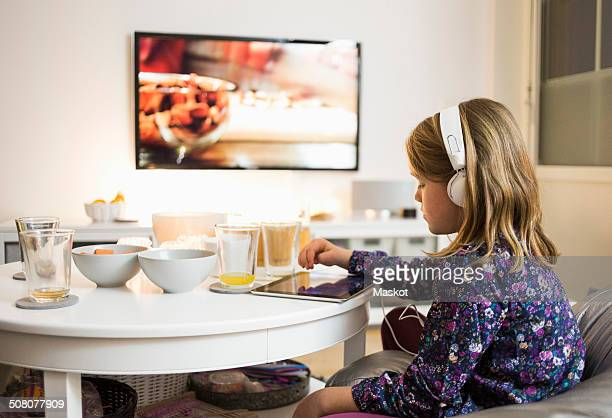 Side view of girl using digital tablet at coffee table in living room
