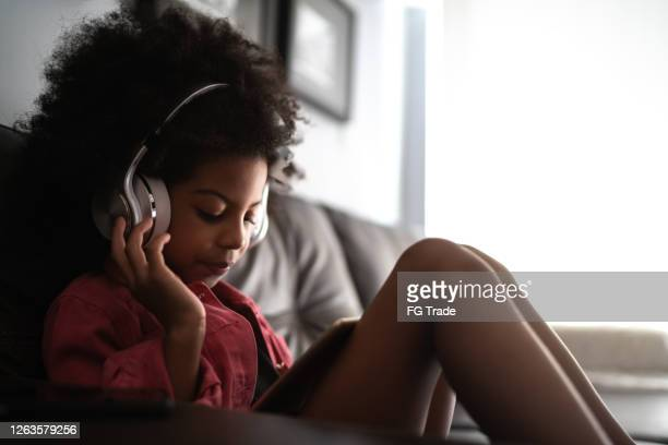 side view of girl using digital tablet at home, listening on headphones - watch what happens: live stock pictures, royalty-free photos & images