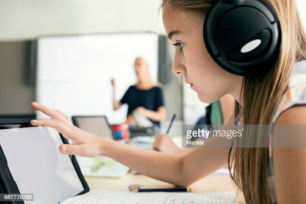 Side view of girl using digital tablet at school
