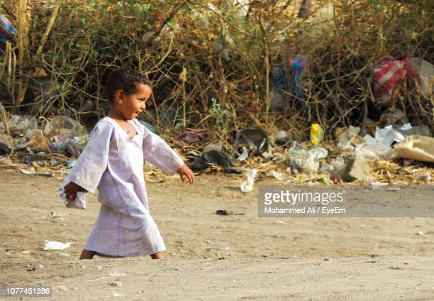 side view of girl walking on dirt road against plants - sudan stock pictures, royalty-free photos & images