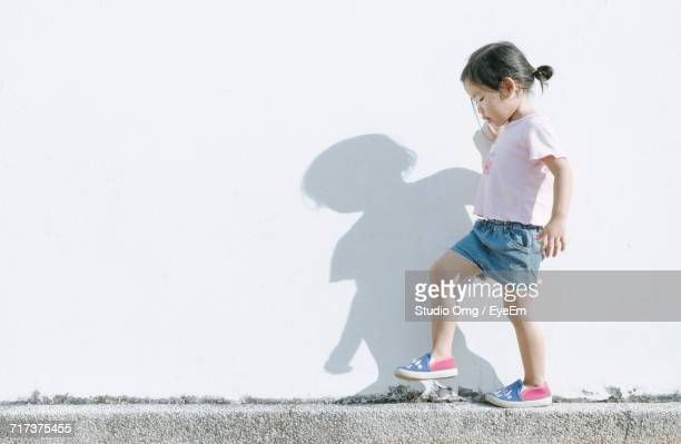 Side View Of Girl Walking On Retaining Wall During Sunny Day