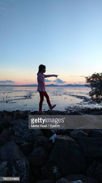 Side View Of Girl Walking On Rocky Beach Against Sky During Sunset