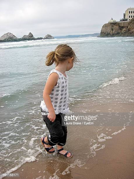 Side View Of Girl Walking On Shore At Beach