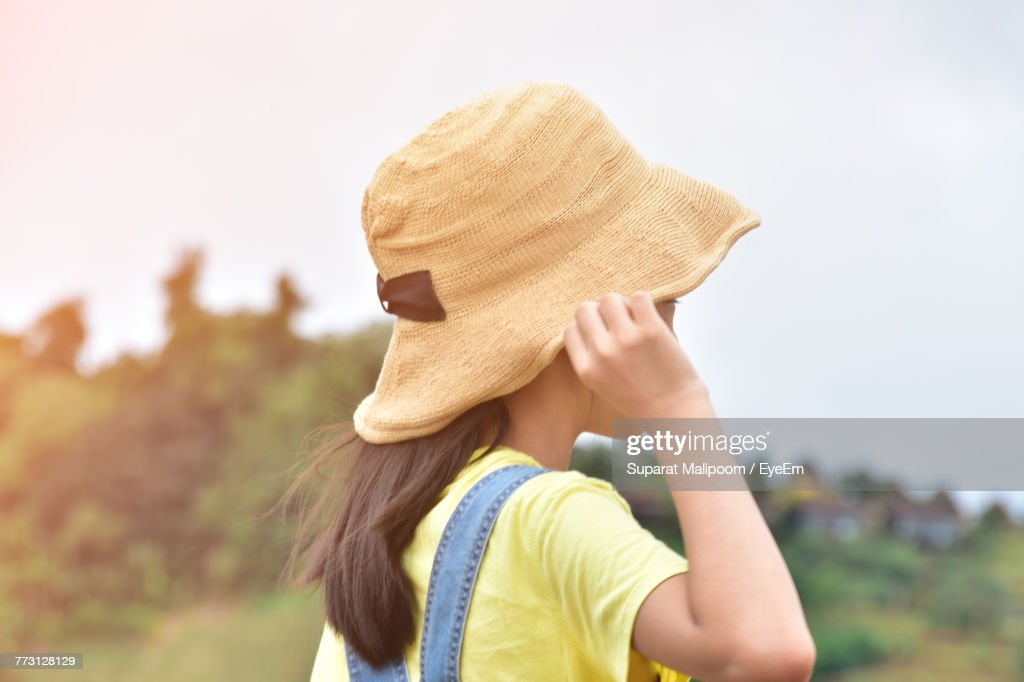Side View Of Girl Wearing Hat Standing On Field : Photo