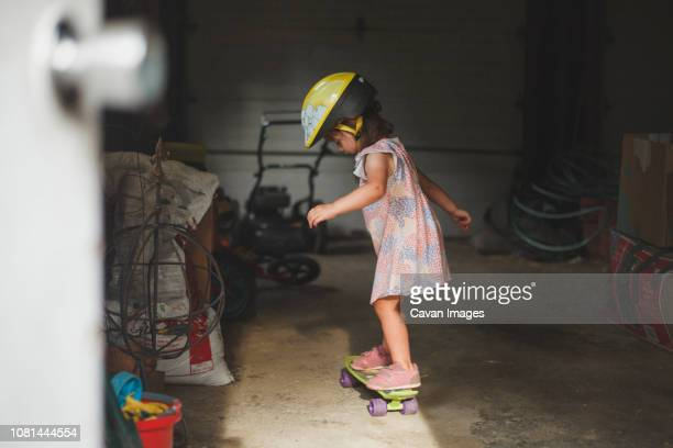 side view of girl wearing helmet while standing on skateboard in garage - tomboy stock photos and pictures