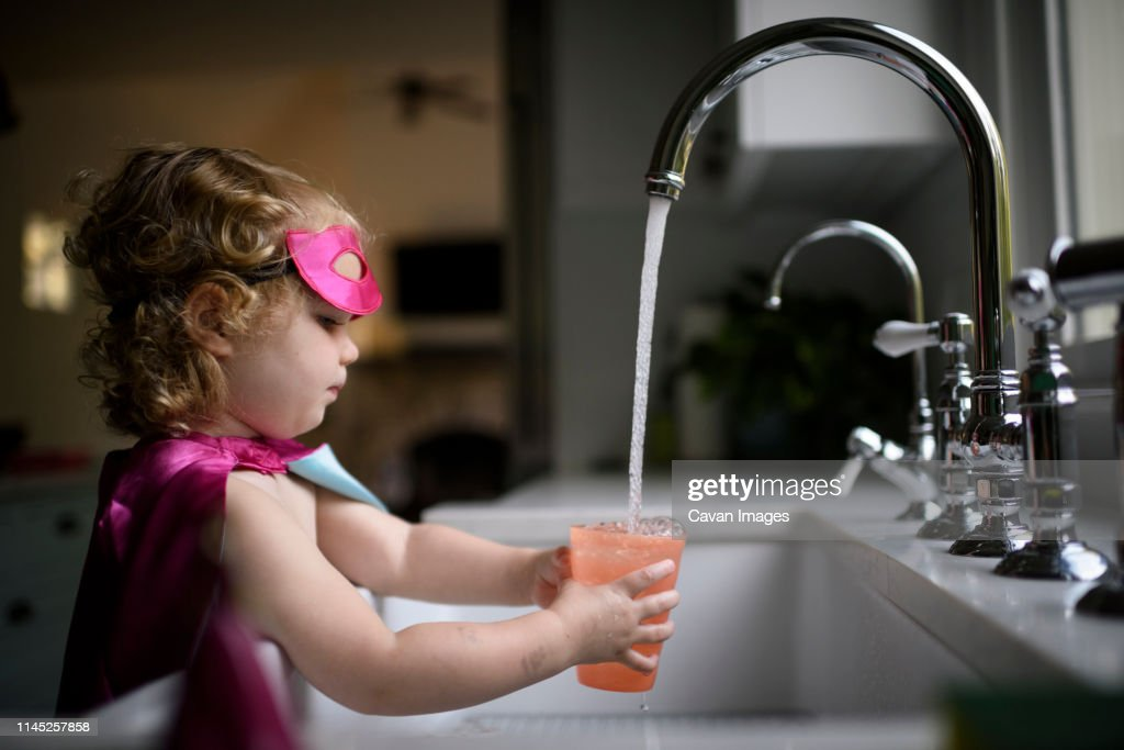 Side view of girl wearing superhero costume filling water in drinking glass while standing at home : Stock Photo