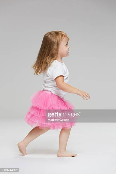 Side view of girl wearing tutu playing against gray background