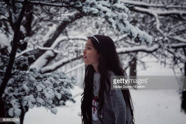 side view of girl with long hair standing on snow covered field - niklas storm eyeem stock photos and pictures