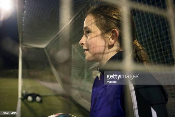 side view of girl with soccer ball seen through goal post net - torpfosten stock-fotos und bilder