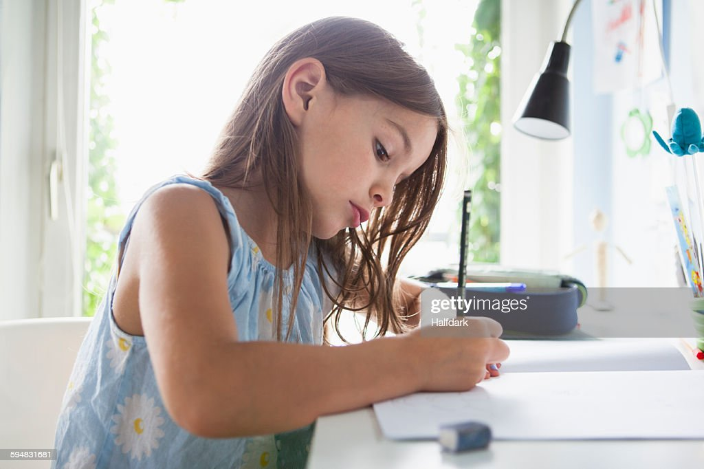 Side view of girl writing in book on table at home : Stock-Foto