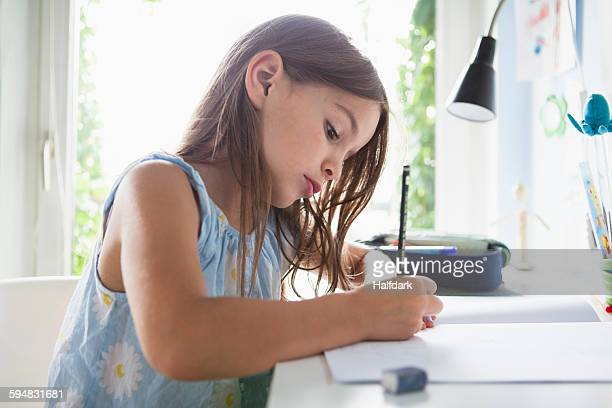 Side view of girl writing in book on table at home