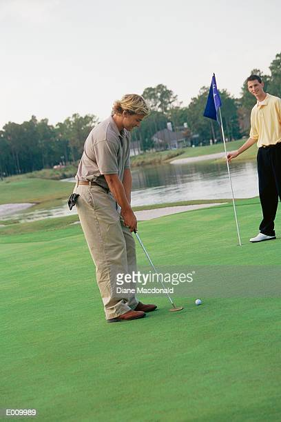 side view of golfer about to take shot - amateur stock pictures, royalty-free photos & images
