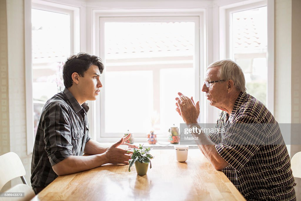 Side view of grandfather and grandson communicating while having coffee : Stock Photo