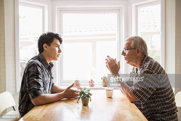 Side view of grandfather and grandson communicating while having coffee