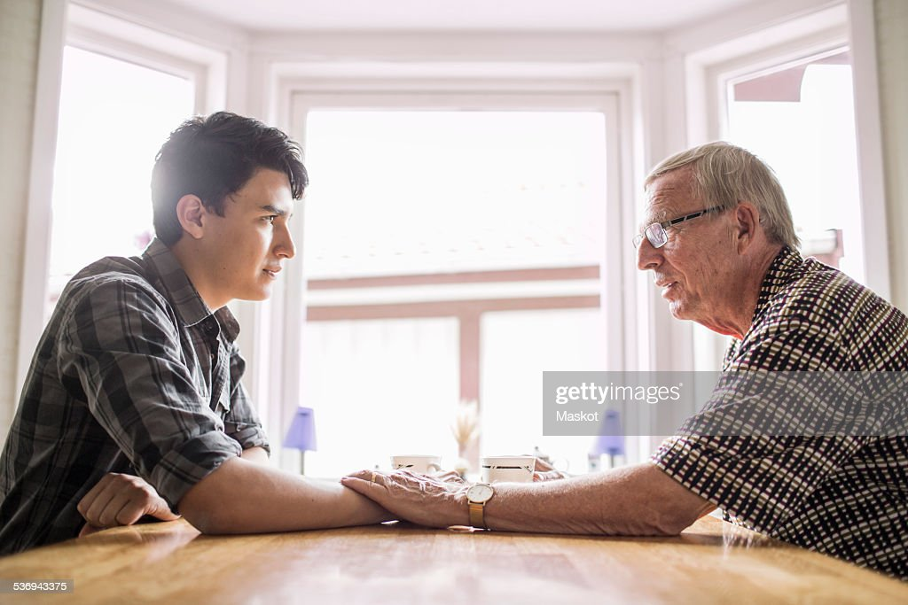 Side view of grandfather consoling grandson at table : Stock Photo