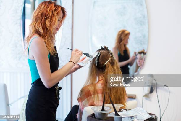 side view of hairdresser applying dye to customers hair - dye stock pictures, royalty-free photos & images