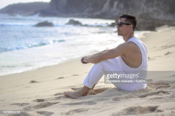 Side View Of Handsome Man Sitting On Sand At Beach