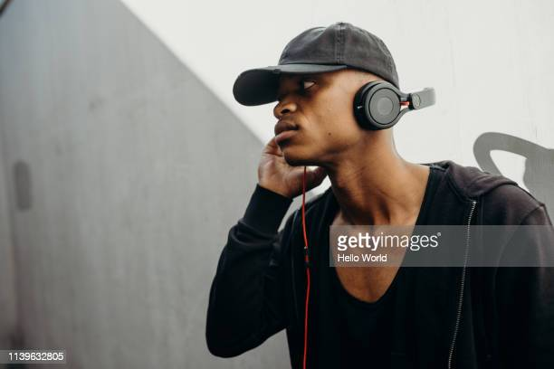 Side view of handsome young man wearing black listening to music with earphones