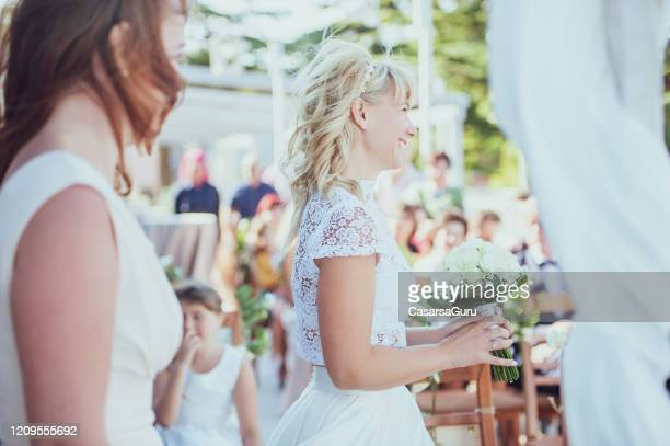 side view of happy bride holding bouquet in outdoors wedding aisle - stock photo - bridesmaid stock pictures, royalty-free photos & images