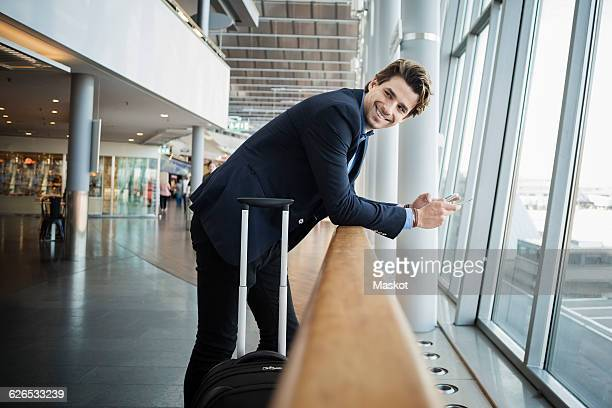 Side view of happy businessman leaning on railing at airport