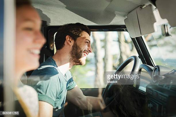side view of happy couple enjoying road trip - auto stockfoto's en -beelden