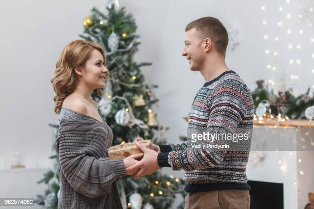 Side view of happy couple standing with present by Christmas tree at home
