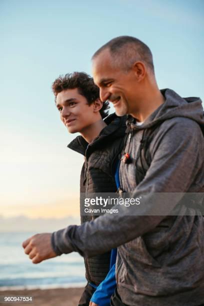 side view of happy father and son walking at beach against sky - familia con un hijo fotografías e imágenes de stock
