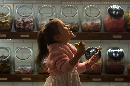 Side view of happy girl holding candies while standing in shop - gettyimageskorea