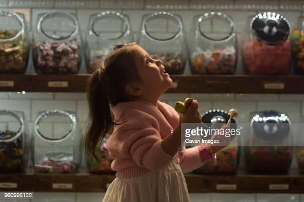 side view of happy girl holding candies while standing in shop - kuchen und süßwaren stock-fotos und bilder