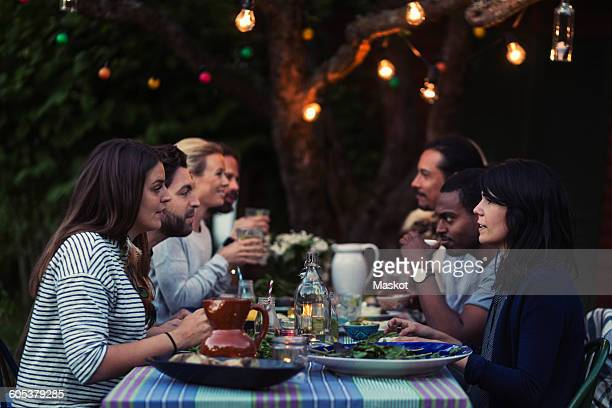 Side view of happy multi-ethnic friends having dinner at table in yard