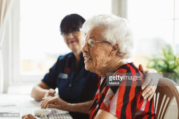 Side view of happy senior woman sitting with caretaker at home