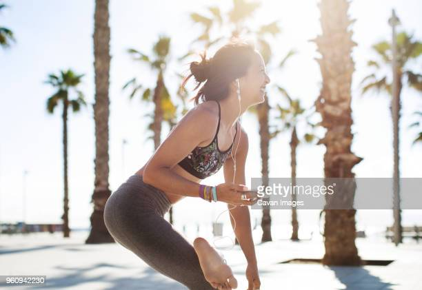side view of happy sporty woman standing on one leg while listening music on beach - zen like stock pictures, royalty-free photos & images