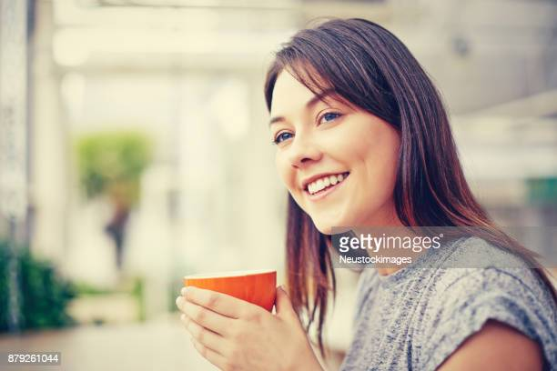 Side view of happy woman holding coffee mug at cafe