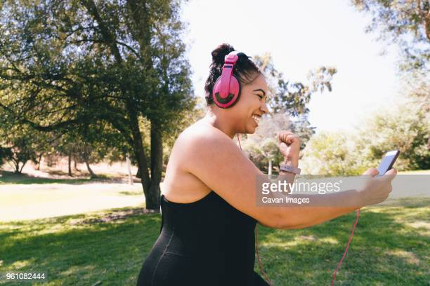 side view of happy woman looking at smart phone while listening music at park - femmes d'âge moyen photos et images de collection