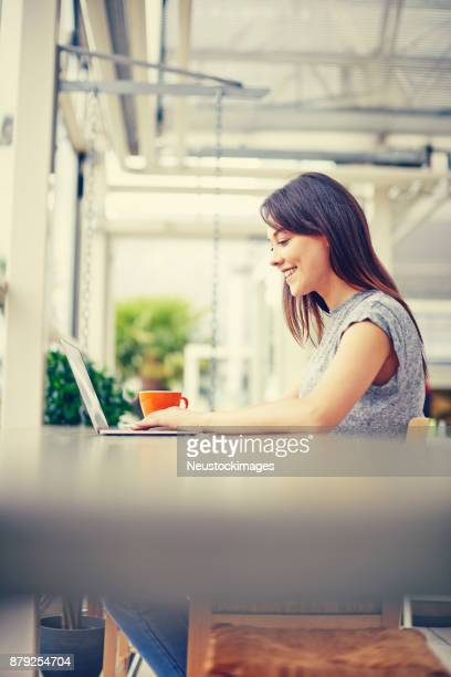Side view of happy woman using laptop in coffee shop