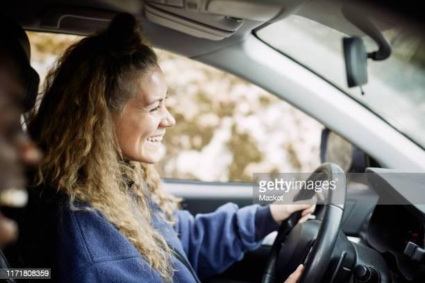 side view of happy young woman driving car - landvoertuig stockfoto's en -beelden