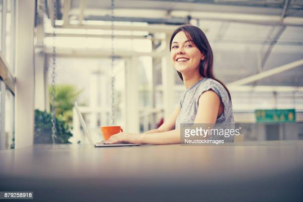 Side view of happy young woman sitting with laptop at cafe table.