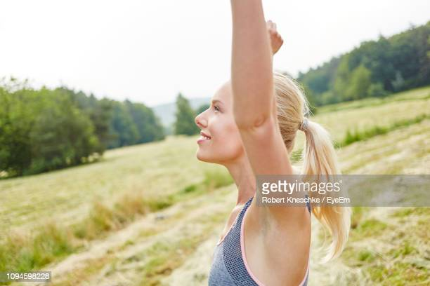 side view of happy young woman standing with arms raised on field - armpit woman stock pictures, royalty-free photos & images