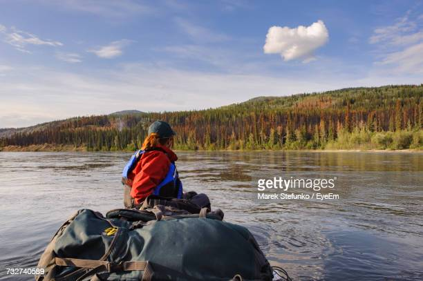 side view of hiker canoeing on river against cloudy sky at forest - marek stefunko stock pictures, royalty-free photos & images