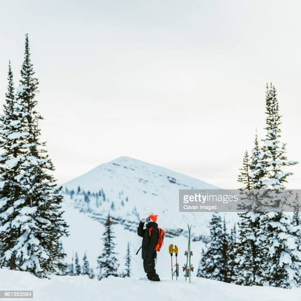 side view of hiker having drink while standing against snowcapped mountain and clear sky - ski holiday stock photos and pictures