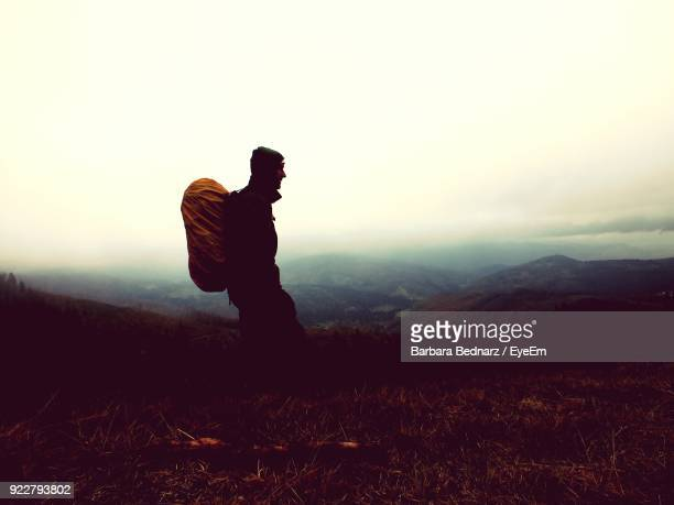 Side View Of Hiker On Mountain Against Sky